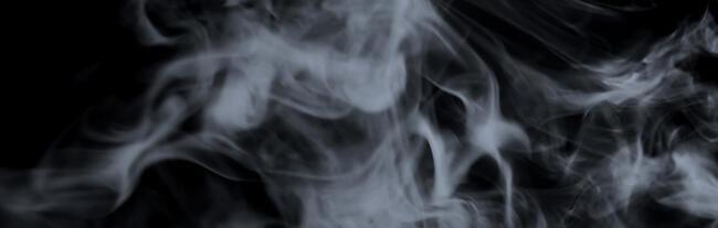 white whispy smoke floats in front of a black background